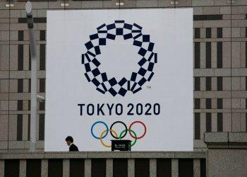 Un hombre pasa junto a un gran cartel promocionando los Juegos Olímpicos de Tokio 2020 en Tokio,  marzo de 2020. Foto: AP Foto/Jae C. Hong.