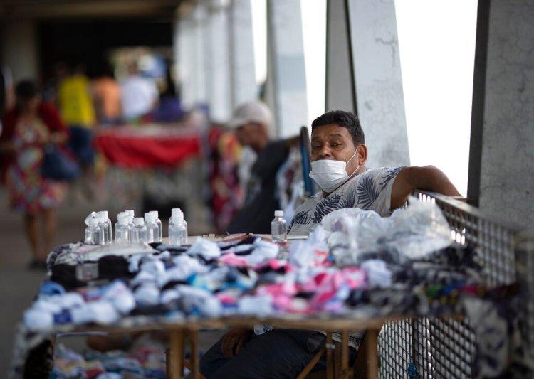 Un vendedor ambulante vende alcohol y máscaras faciales para protegerse contra la propagación del nuevo coronavirus en una estación de tren en Río de Janeiro, Brasil, el lunes 16 de marzo de 2020. (Foto AP/Silvia Izquierdo)