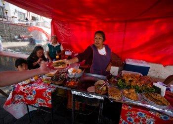 Una mujer sirve tacos en un puesto callejero en San Andrés Mixquic, en las afueras de la Ciudad de México, el lunes 30 de marzo de 2020. Foto: Fernando Llano/AP.