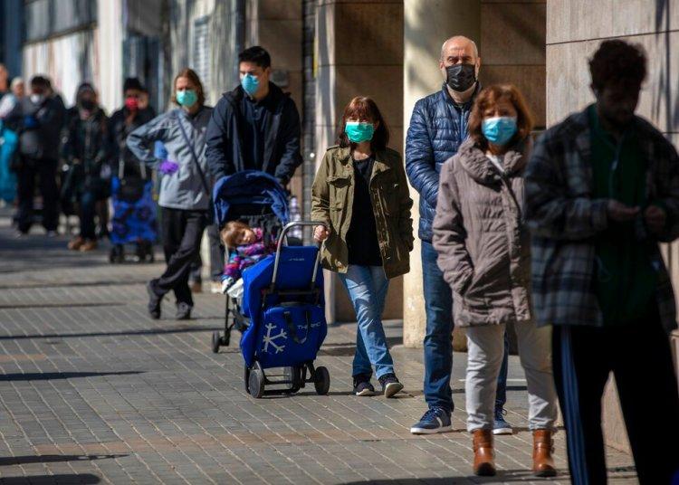 Personas con mascarillas hacen cola en una tienda de Barcelona. Foto: Emilio Morenatti/AP.