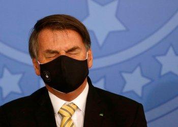 El presidente Jair Bolsonaro, con un nasobuco para protegerse del coronavirus, cierra brevemente los ojos durante un evento el viernes 15 de mayo de 2020, en el palacio presidencial de Planalto, Brasilia. Foto: Eraldo Peres/AP.