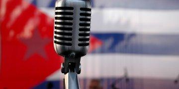 Una bandera cubana y un micrófono de antaño, resumen a la perfeción la identidad de Juan Formell y los Los Van Van.