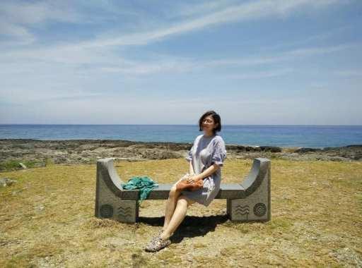 jeune femme assise sur un banc devant la mer