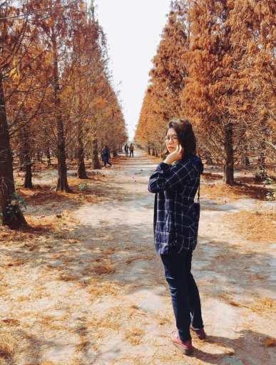 femme debout dans une allée d'arbres à l'automne