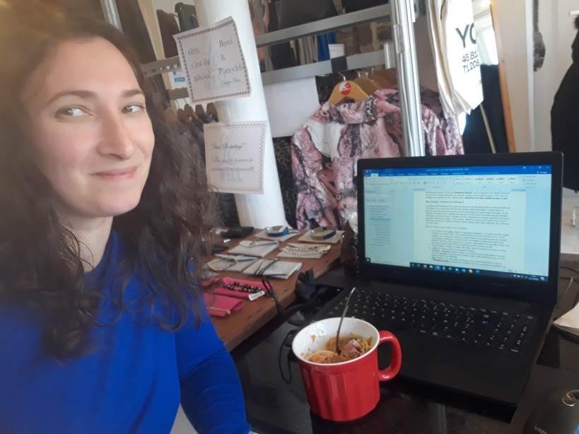 femme dans une boutique de prêt-à-porter devant son ordinateur
