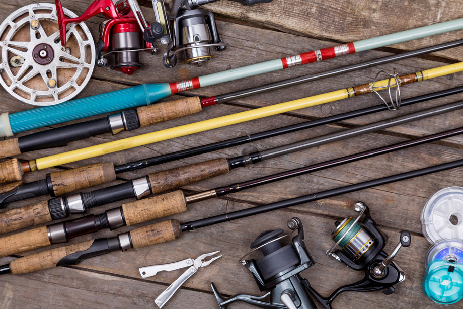 Fishing Rods And Reels On Wooded Floorboards