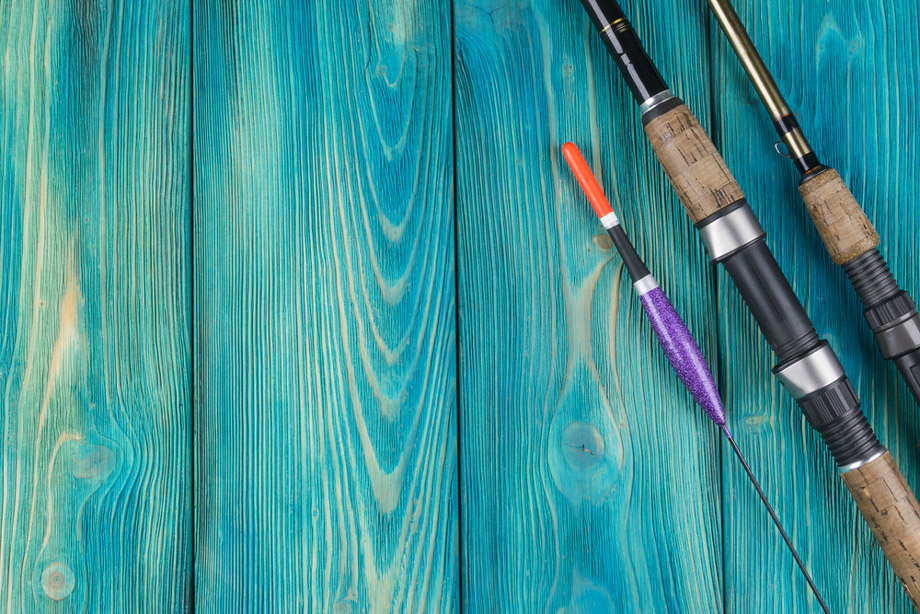 Fishing Rods On A Blue Wooden Background