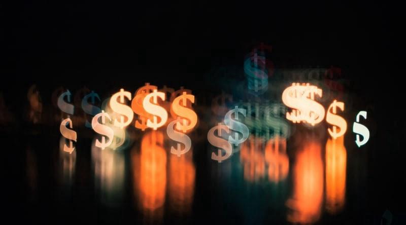 Illuminated dollar sign lights against a black background