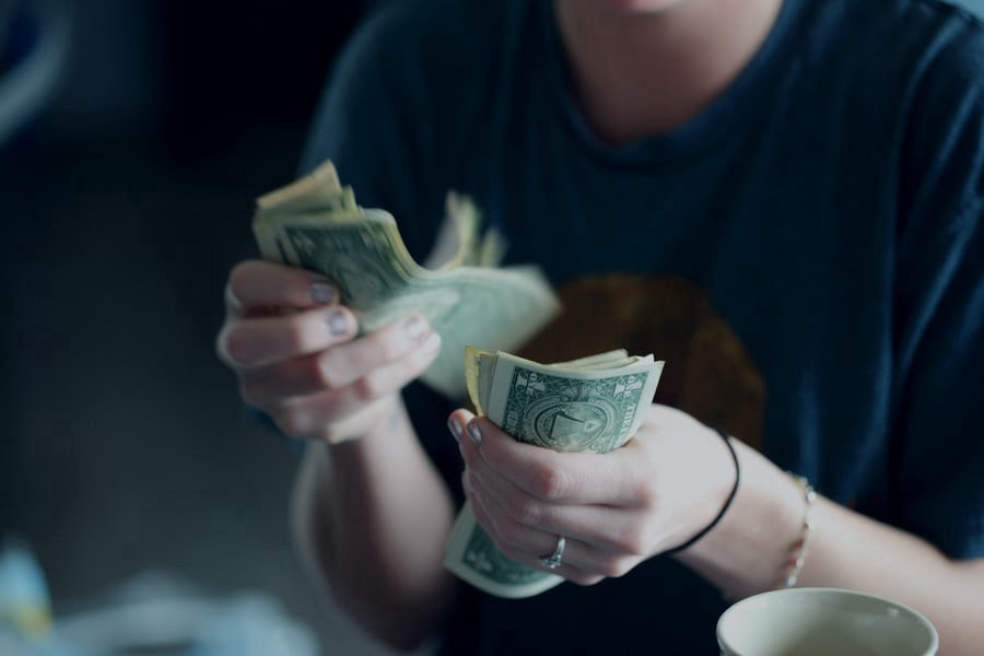 Person holding a stack of USD $1 bills and counting them