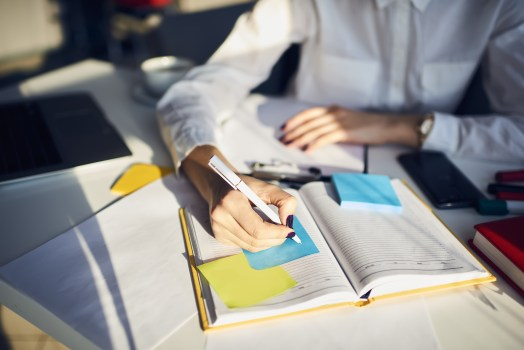 Lady in white dress shirt taking notes in a notebook