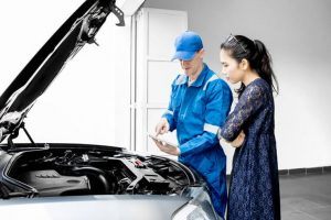 Girl learning how to fix car