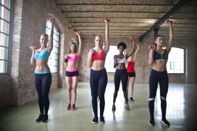 women assorted sports bras raising their pink dumbbells