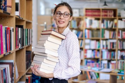 Pictured: a librarian holding a stack of books