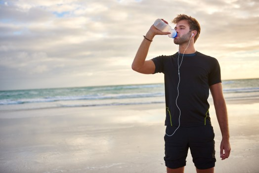 image of young man drinking water on the beach to avoid getting sick during exams