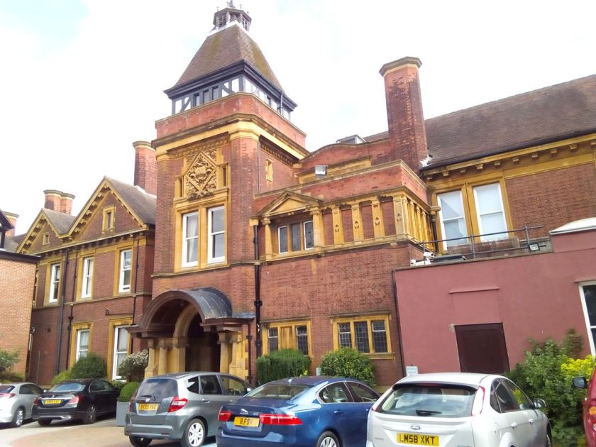 Front view of the The Exchange - Bartley Hall. There are cars parked outside the building.