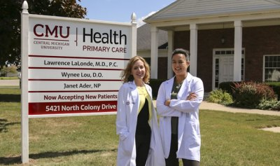 Students from CMU in front of health clinic sign.