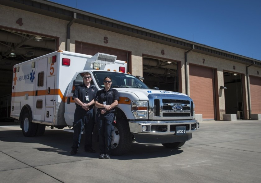 Two paramedics on the side of the ambulance