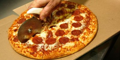 A man is slicing pizza