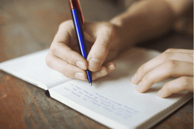 A man writing on diary with pen