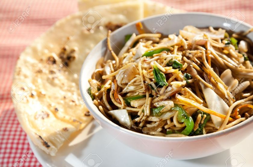 an image of a delicious plate of noodles with bread on the side
