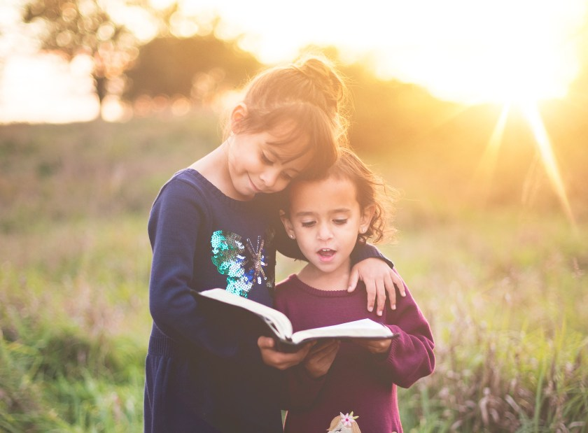 two kids reading the bible outside