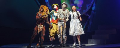 4 people standing at stage in different costumes