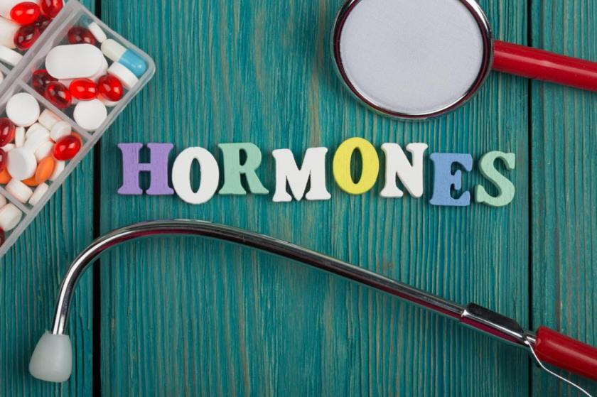 picture of the word hormones spelled out with a stethoscope and pills on the table