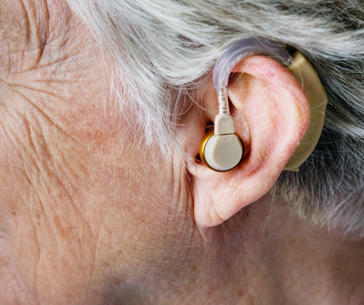 Picutre of a person with an earpiece that helps them hear