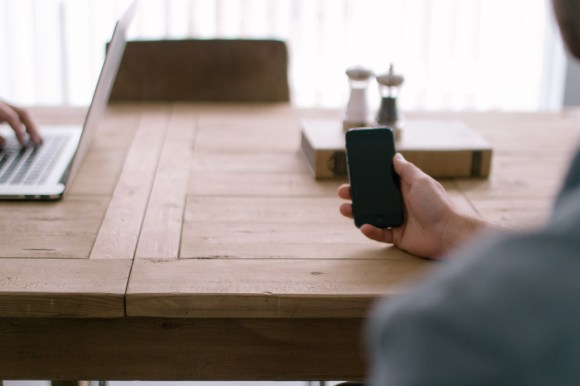 person-smartphone-office-table