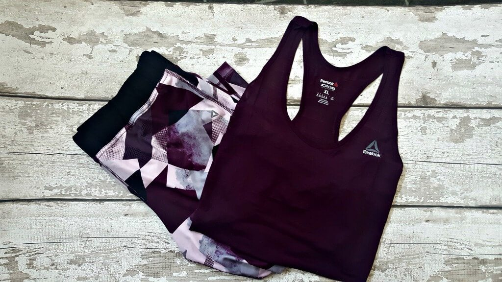 flatlay of a plus size active wear outfit in deep purple on a background for return to fitness post