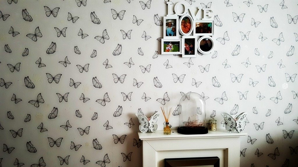 home renovations - white fireplace against white wallpaper with butterflies on and a photo frame hanging above with the word love