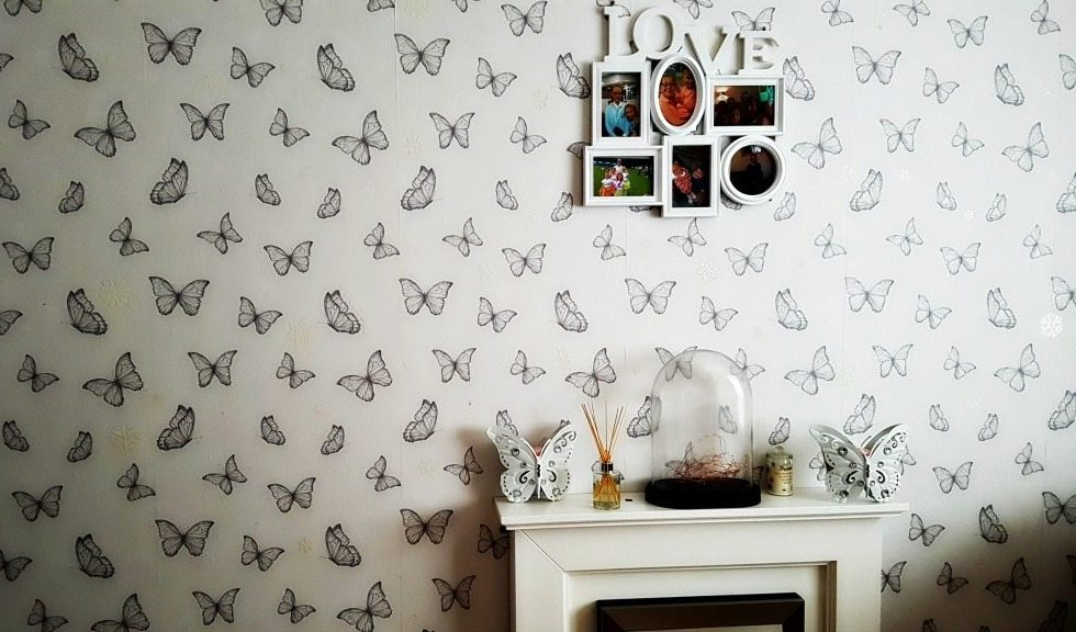 home improvements - white fireplace against white wallpaper with butterflies on and a photo frame hanging above with the word love