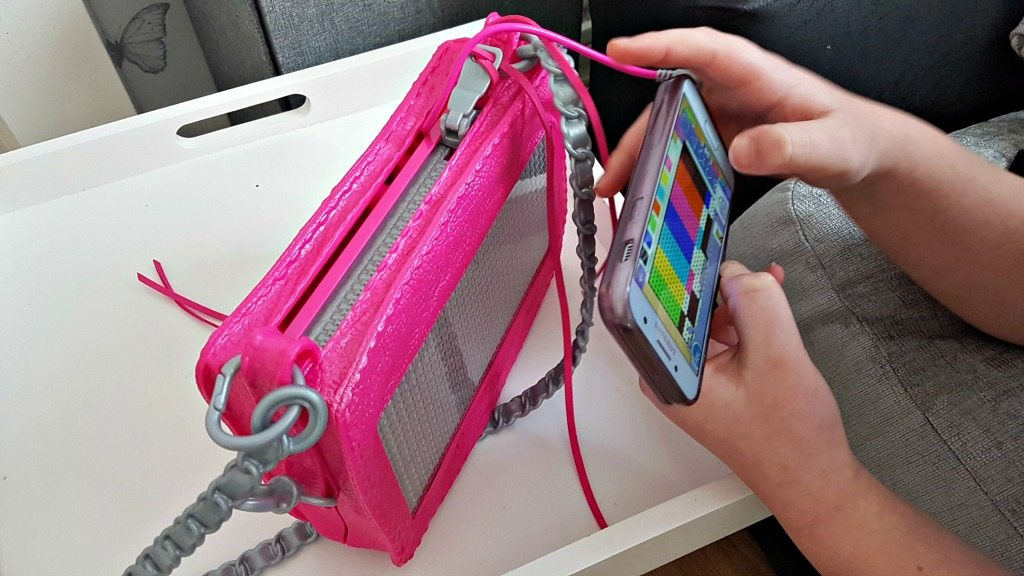 a phone connected to the project mc2 pixel purse being held as a design is created on the app