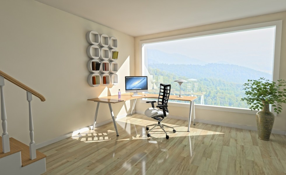 an open plan room with wooden flooring and full length window with a desk and chair in the corner and cube shelving on the wall