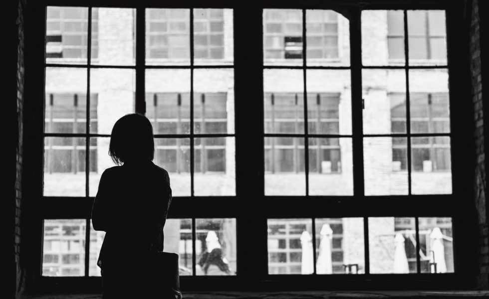 grey scale image of a woman standing alone in front of a large window