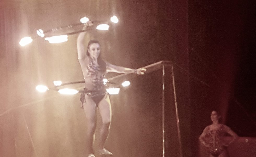 circus performer with hoops of fire on a ball