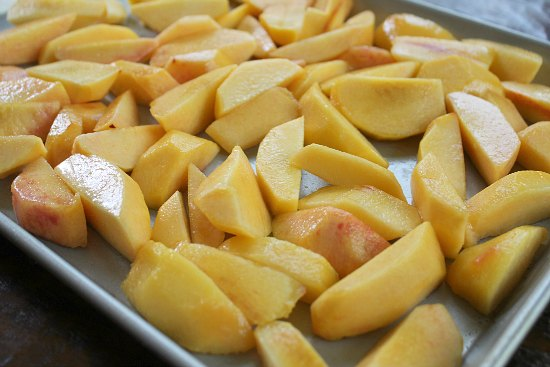 sliced peaches on cookie sheet