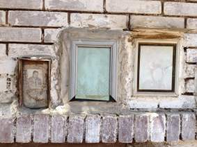 Photos, mementos and flowers don the crumbling mausoleums of the cemetery behind the Convent of St. George