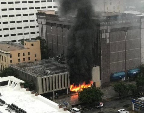 Photo of an office building with fire shooting out of the windows and black smoke in the air.