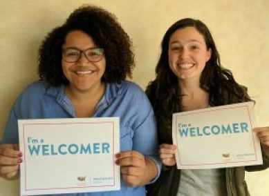 """OneJustice staff hold up signs saying """"I'm a welcomer"""""""