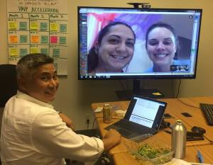 Two attorneys shown on a large computer screen with the supervision immigration attorney at a table in the OneJustice conference room.