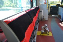 This public bus had fold down seats along the front lower section and straps for securing wheelchairs and the like. The seats are up when not occupied.