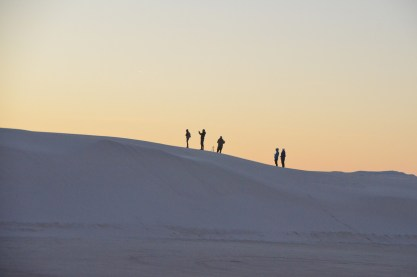 Folks watching the sunset from atop a dune.