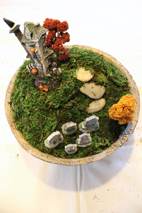 Halloween terrarium with a house on a hill and a graveyard