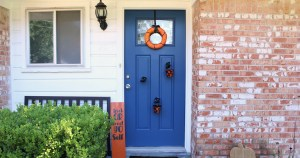 Black and orange Halloween porch / wreath, sign, and buckets of candy held by mannequin hands