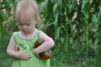 Pensive girl with tomatoes (and corn in background)