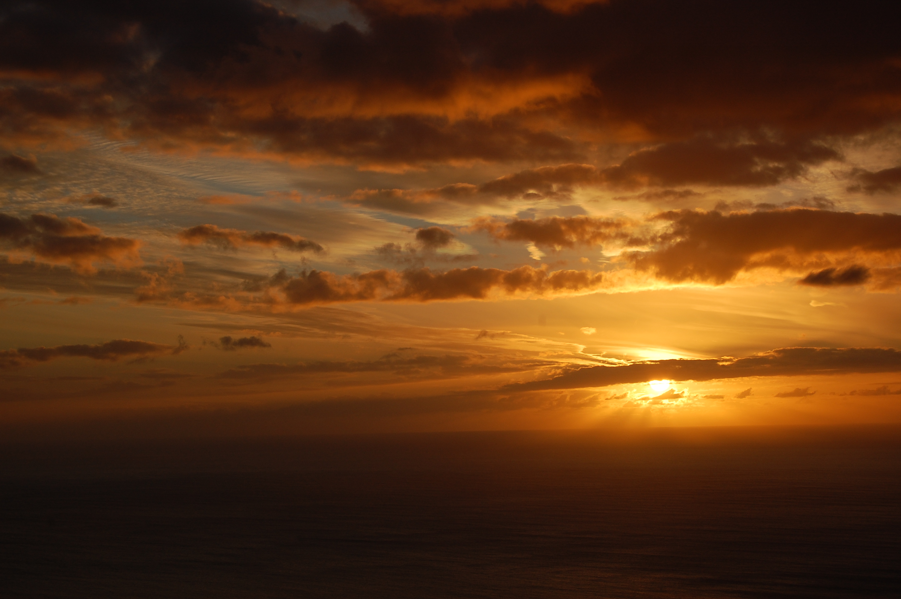 An amber coloured sunset with shafts of light coming through clouds over the sea.