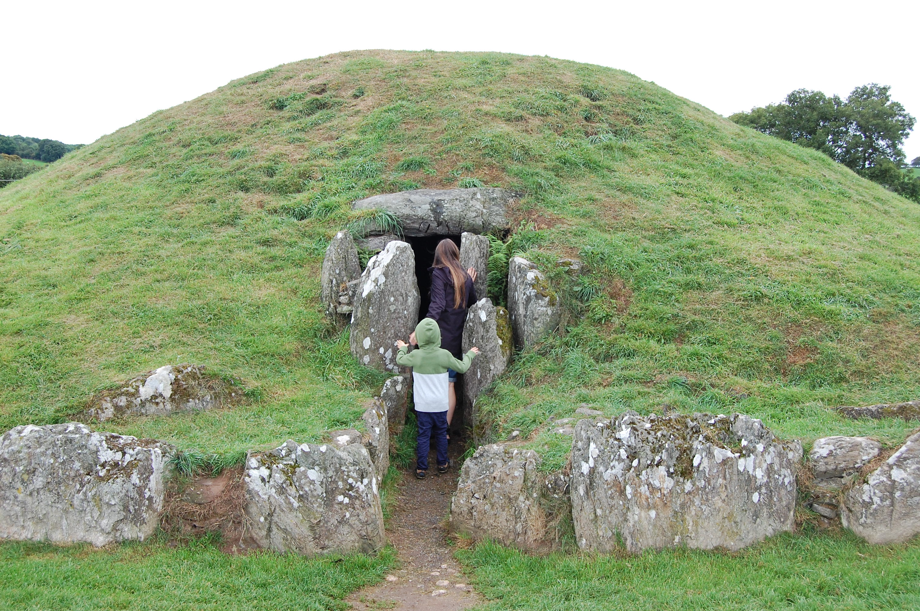 The author and her son heading into the opening of an ancient burial site ringed by stones and topped by a grassy mound.