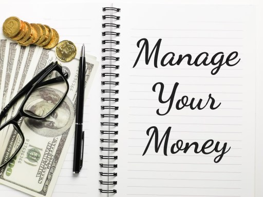 Manage Your Money, written in a notebook with bills. coin, pen and glasses