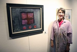 Photo of artist Catherine Peck with her painting